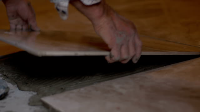 Tiler laying a tile on the floor video