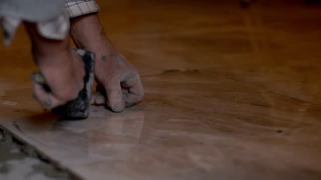 Tiler tiling the floor video