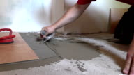 Tiler worker hand spread adhesive material. Left side sliding video