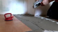 Tiler worker hand spread adhesive material. Right side sliding video