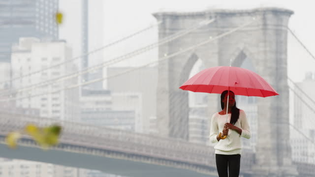 Tilt down of a woman holding an umbrella as she walks away from the Brooklyn Bridge in slow motion video