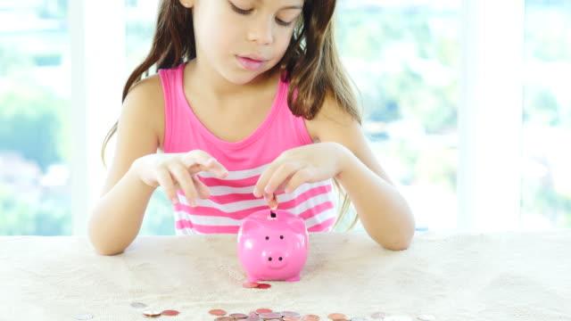 Tilt downshot of little girl and piggy bank video