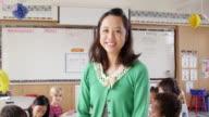 Tilt shot of female Asian school teacher in front of class video