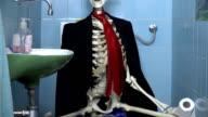 Tilt shot of skeleton in business clothes sitting on toilet video