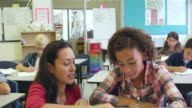 Tilt shot of teacher helping pupil at her desk, shot on R3D video