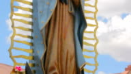 Tilt to Reveal a Statue of the Virgin Guadalupe and an Adobe Catholic Church video