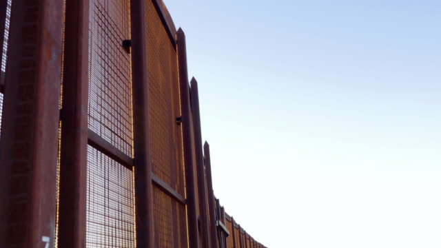 Tilt to Reveal the Border Fence Between Mexico and America - 4K video