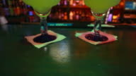 Tilt up of two Margaritas sitting at colorful bar video