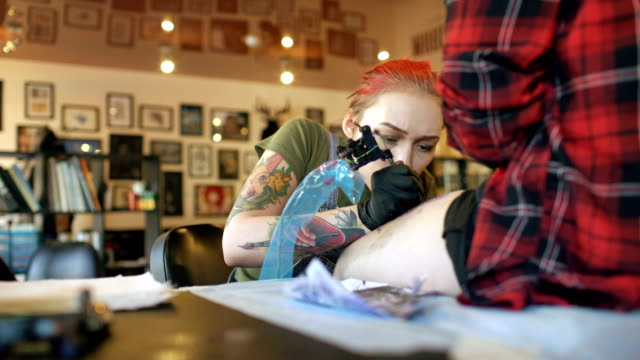 Tilt up shoot of young red haired woman tattoo artist tattooing picture on leg of young girl client in studio video
