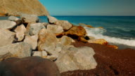 Tilting Shot of a Mediterranean Volcanic Beach with Red Sand and Surf Hitting the Rocks video