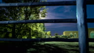 Tilt-up time lapse of operating horse-breeding farm surrounded by a wooden fence and trees against night sky with moving clouds. video