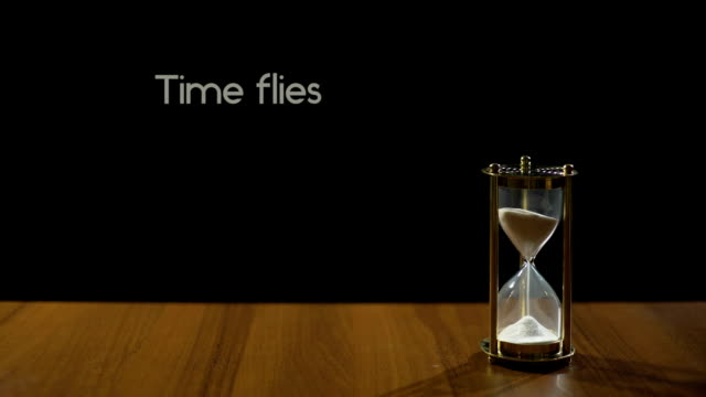 Time flies, phrase about transience of life, sand flowing in hourglass on table video