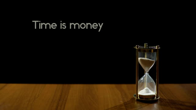 Time is money, wise phrase against black background, sand flowing in hourglass video