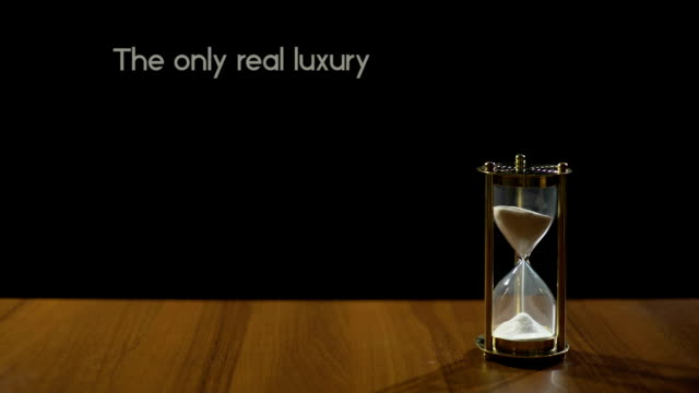 Time is only real luxury, popular phrase about life value, sandglass on table video
