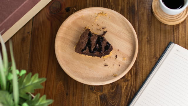 Time Lapse : Eating brownie chocolate cake on wooden dish and wooden table video