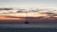 4K Time Lapse footage of Sunset at Koh Chang beach with anchored boat floating around. video