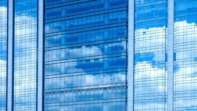 Time lapse, looking up at a glass-covered skyscraper, reflecting the blue sky and passing clouds video
