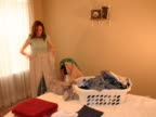Time lapse of a young woman folding clothes NTSC video