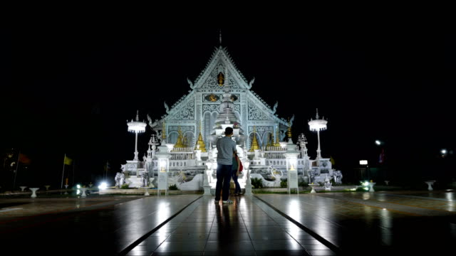 Time Lapse of ancient burma temple turn on multi color light at night. wat chiangrai, lampang, thailand video