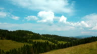 Time lapse of clouds and beautiful green mountains with coniferous trees video