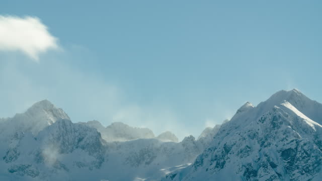 Time lapse of clouds flowing over snow covered mountain peaks in Austrian Alps video