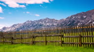 Time lapse of clouds moving over mountains and fence video