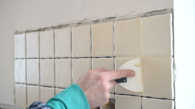 Time lapse of filling gaps between tiles with grout video