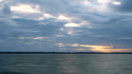 Time lapse of gorgeous clouds at dawn over water video
