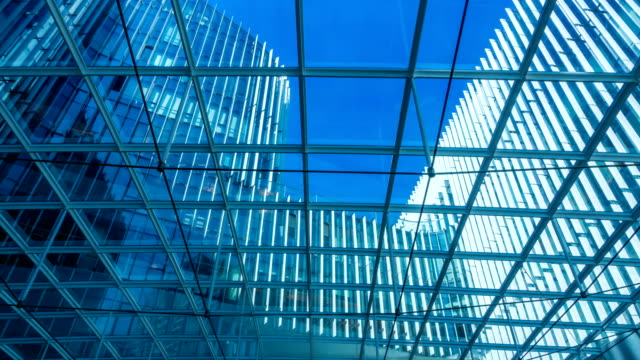 Time lapse of Looking up through the sun roof at office building at clouds and sunshine. video