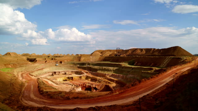 Time lapse of open-cast. Operating mine. Bauxite quarry. Excavators load ore into dump-trucks. This area has been mined for buaxite, aluminum and other minerals. video