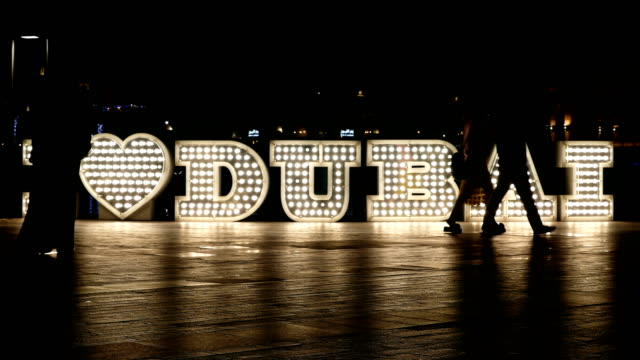 Time lapse of people passing by in front of lighted 'I love Dubai' logo at night, 4k video