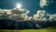Time lapse of sun emerging from clouds over mountain video