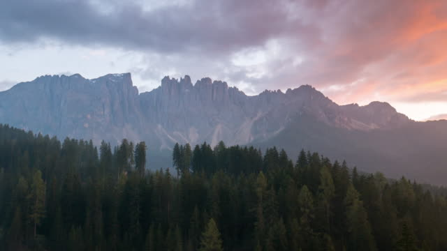 Time Lapse of sunset sky and cloudy in carezza lake and pine tree , dolomites south tyrol Italy video