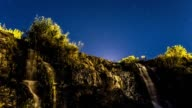 Time lapse of waterfall next to stars moving the sky video