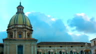 Time lapse of white puffy clouds over a blue sky with a mediterranean church on the background video