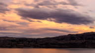 Time lapse pastel colored sunset clouds over lake video