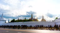 Time Lapse shot of Massive People walking on Road with Thai Temple Background, Bangkok, Thailand. Zoom in shot. video