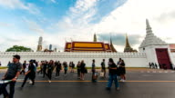 Time Lapse shot of Massive People walking on Road with Thai Temple Background, Bangkok, Thailand. Tilt up shot. video