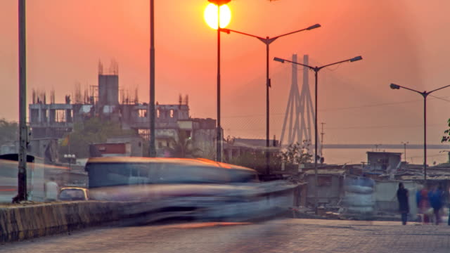 Time lapse shot of sun setting against the Bandra worli sea-link also known as Rajiv Gandhi sea link, while moving traffic and people in the foreground, Mumbai, India video