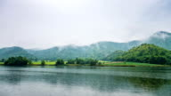Time lapse video of Beautiful Lake in front of Twin mountains with fog and cloudy sky. video