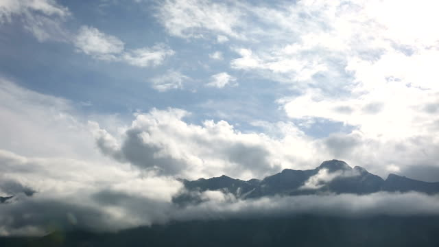 Time lapse view of clouds lifting above mountains video