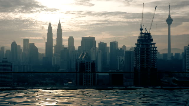 Time lapse view of swimming pool on the skyscraper roof against sunrise building cityscape. Kuala Lumpur, Malaysia video