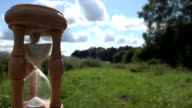 Time measure with wooden sandglass on fields and sky background. FullHD video