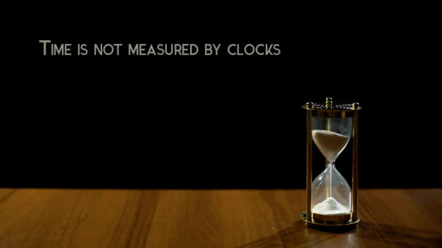 Time measured by moments not clocks, phrase about life value, sandglass on table video