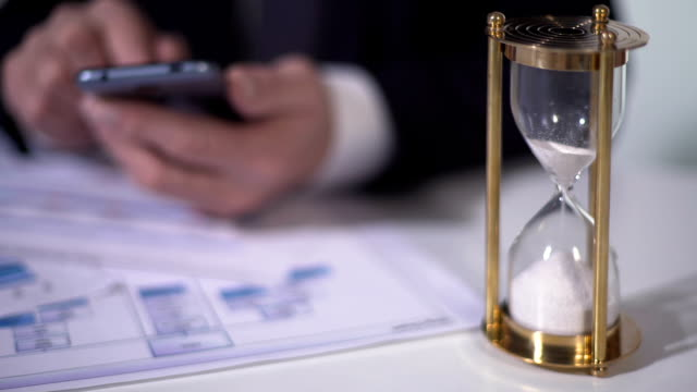 Time running out with sand in hourglass, defocused man using smartphone for work video
