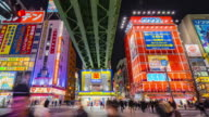4K Time-lapse : Crowds across road below colorful signs in Akihabara. (zoom in camera view) video