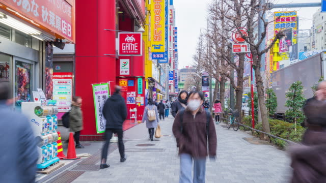 4K Time-lapse : Crowds below colorful signs in Akihabara. The historic electronics district has evolved into a shopping area for video games, anime, manga, and computer goods. video