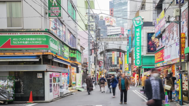 4K Time-lapse : Crowds on road below colorful signs in Akihabara. The historic electronics district has evolved into a shopping area for video games, anime, manga, and computer goods. video