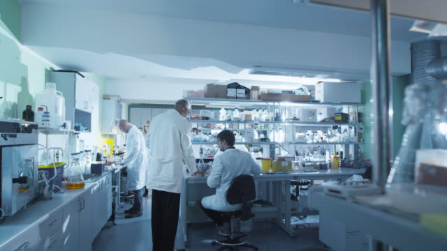 Timelapse footage of a team of scientists in white coats that are working in a modern laboratory. video