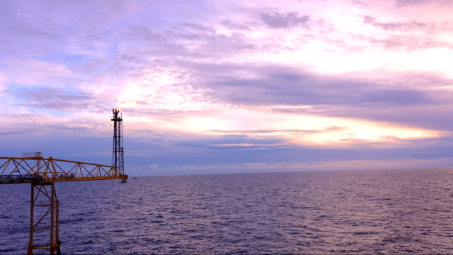 Timelapse footage of oil and gas platform with flare burning bridge with sun rise and beautiful clouds in the morning for oil and gas industry concept. video